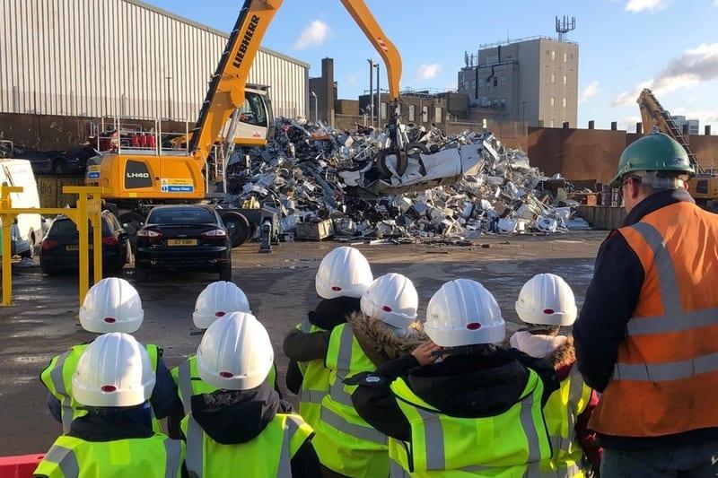 Children being shown round scrap metal site